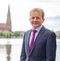 Dr. Rico Badenschier vor der Silhouette der Stadt Schwerin mit Pfaffenteich und Dom