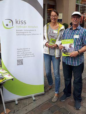 Aktionstag Sucht: Kirsten  Sievert (li) und Roland Loeckelt (re) mit dem Selbsthilfejournal und anderen Informationsmaterialien am Infostand der KISS in der Schweriner Mecklenburgstraße